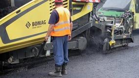 Byggande i Polen Arbetare som applicerar ny asfalt Royaltyfria Bilder