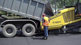 Byggande i Polen Arbetare som applicerar ny asfalt Arkivfoton