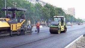Byggande i Polen Arbetare som applicerar ny asfalt Arkivfoto