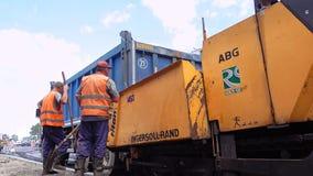 Byggande i Polen Arbetare som applicerar ny asfalt Royaltyfria Foton