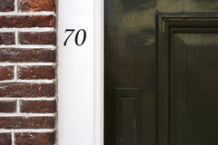 Byggande ingång med den mörka tegelstenväggen och husnummer i Amsterdam Royaltyfri Bild