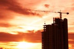 Byggande kran och byggande solnedgång Royaltyfri Foto