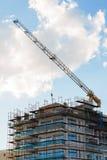Byggande kran och byggande under konstruktion mot blå himmel Royaltyfria Bilder