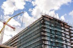 Byggande kran och byggande under konstruktion mot blå himmel Arkivbild