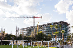 Byggande kran och byggande under konstruktion mot blå himmel Arkivfoton