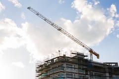 Byggande kran och byggande under konstruktion mot blå himmel Royaltyfri Foto