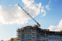 Byggande kran och byggande under konstruktion mot blå himmel Royaltyfria Foton