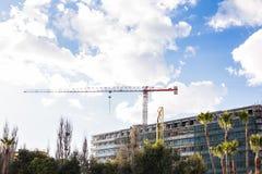 Byggande kran och byggande under konstruktion mot blå himmel Arkivbilder