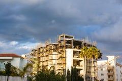 Byggande kran och byggande under konstruktion mot blå himmel Royaltyfri Fotografi