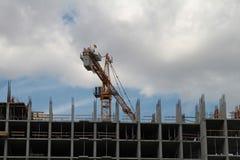 Byggande kran och byggande under konstruktion mot blå himmel Arkivfoto
