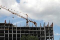 Byggande kran och byggande under konstruktion mot blå himmel Royaltyfri Bild