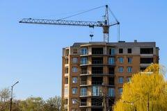 Byggande kran och byggande under konstruktion mot blå himmel Fotografering för Bildbyråer