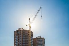 Byggande kran och byggande under konstruktion mot en blå himmel i solljuset Royaltyfri Bild