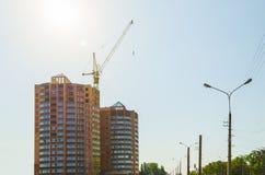 Byggande kran och byggande under konstruktion mot en blå himmel i solljuset Royaltyfria Foton