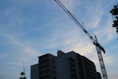 Byggande kran och byggande under konstruktion tegelstenkonstruktion som utomhus lägger lokalen Konstruktionskranar och hög lönefö Royaltyfri Fotografi