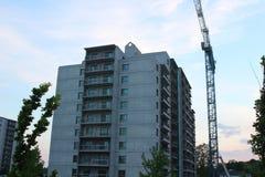 Byggande kran och byggande under konstruktion tegelstenkonstruktion som utomhus lägger lokalen Konstruktionskranar och hög lönefö Royaltyfri Bild