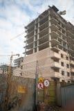 Byggande kran på bakgrunden av envåning byggnad under konstruktion Arkivfoto