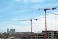 Byggande kranar och byggande under konstruktion mot molnig himmel Royaltyfri Foto