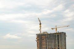 Byggande kranar och byggande under konstruktion på blått molnigt s Arkivbild