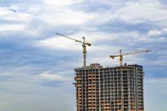 Byggande kranar och byggande under konstruktion på blått molnigt s Fotografering för Bildbyråer