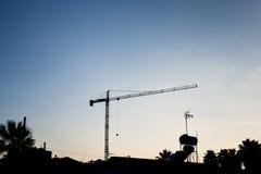 Byggande krankontur och byggande under konstruktion mot blå himmel Royaltyfri Fotografi