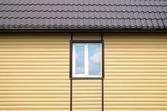 Byggande metall taklägger och den färdiga väggen med beigea sidingpaneler med det vita plast- fönstret Arkivbild