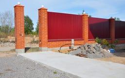 Byggande nytt metallstaket med dörren, port av yttersida för vägg för röda tegelstenar för modern stildesign dekorativ med cement royaltyfria foton