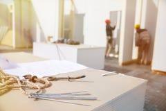 Byggande plan och arbetare i bakgrunden Arkivfoto