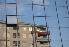 Byggande reflexion i annat byggnadsfönster arkivbild