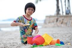 Bygger den asiatiska flickan för ståenden med glasögon sandslotten på stranden vid färgrika modeller royaltyfri bild