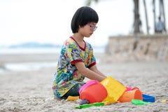 Bygger den asiatiska flickan f?r st?enden med glas?gon sandslotten p? stranden vid f?rgrika modeller royaltyfria foton