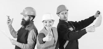 Byggmästare arkitekt, reparatör som är lycklig på arbete Män och kvinna i hjälmar som är upptagna med vita olika uppgifter Royaltyfri Foto