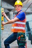 Byggmästare eller arbetare som kontrollerar väggen på konstruktionsplats Fotografering för Bildbyråer