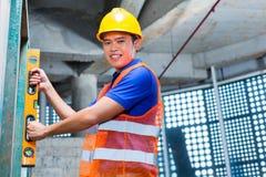 Byggmästare eller arbetare som kontrollerar väggen på konstruktionsplats Arkivfoton