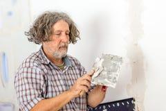 Byggmästare eller husägare som reparerar en vägg Arkivbild