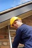 Byggmästare eller roofer som klättrar en stege royaltyfri foto