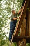 Byggmästare eller snickarearbete och bygganden ett tak arkivbilder