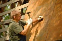 Byggmästare eller snickarearbete och bygganden ett tak arkivfoto