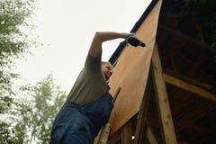 Byggmästare eller snickarearbete och bygganden ett tak royaltyfri foto