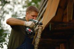 Byggmästare eller snickarearbete och bygganden ett tak arkivbild