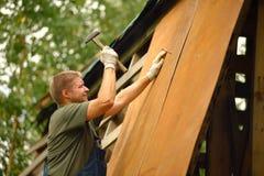 Byggmästare eller snickarearbete och bygganden ett tak royaltyfria foton