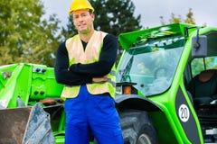 Byggmästare framme av konstruktionsmaskineri Arkivbild