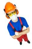 Byggmästare i hardhat, öronskydd, goggles och gasmask arkivbild
