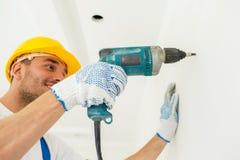 Byggmästare i hardhat med drillborren som perforerar väggen royaltyfria bilder