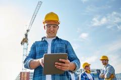 Byggmästare i hardhat med minnestavlaPC på konstruktion royaltyfria bilder