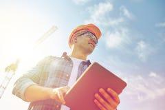 Byggmästare i hardhat med minnestavlaPC på konstruktion arkivbild