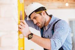 Byggmästare i hardhat med skrivplattan och blyertspennan inomhus arkivbild