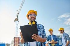 Byggmästare i hardhat med skrivplattan på konstruktion royaltyfri fotografi