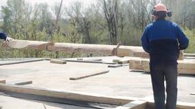 Byggmästare i likformign och hjälmen som fungerar med remmar på konstruktionsområde gem Arbetare som arbetar med en kran på arkivfilmer