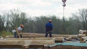 Byggmästare i likformign och hjälmen som fungerar med remmar på konstruktionsområde gem Arbetare som arbetar med en kran på stock video